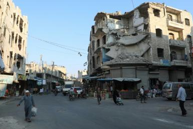 People walk near heavily damaged buildings in the rebel-held city of Idlib in northwestern Syria on September 16, 2019