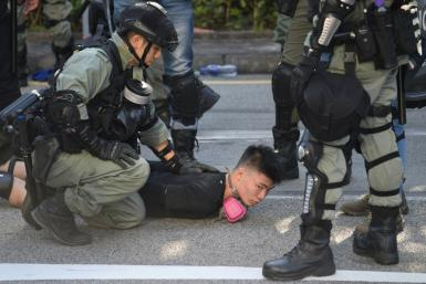 Police detain a demonstrator during protests in Hong Kong's Tuen Mun district