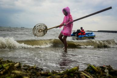 Volunteers in Manila scoop up coastal trash as part of the World Cleanup Day initiative