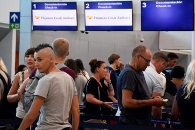 Passengers stand in line at the closed Thomas Cook check-in desk at the airport in Cancun, Mexico, on September 23, 2019