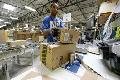 Waning consumer confidence could hit retail sales, a mainstay of the US economy. Employee Lamar Roby prepares shipping orders at Amazon's San Bernardino Fulfillment Center