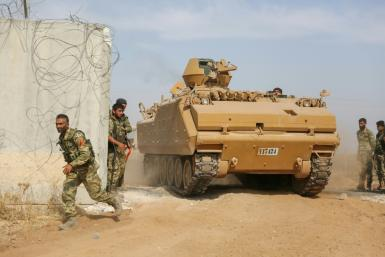 Pro-Turkish Syrian fighters drive an armoured personnel carrier across the border into Syria as they take part in an offensive against Kurdish-controlled areas in northeastern Syria launched by the Turkish military, on October 11, 2019