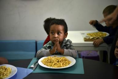 A child prays before eating at the Kapuy Foundation shelter which supports children abandoned, or with serious health problems, including undernourishment in Venezuela