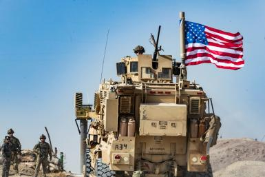 A US soldier sits atop an armored vehicle during a demonstration by Syrian Kurds in the town of Ras al-Ain shortly before the Turkish invasion in October 2019