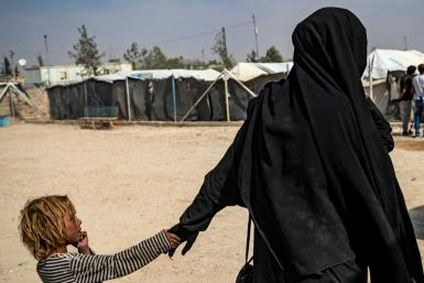 A French woman held at Al-Hol camp holds a child by the hand