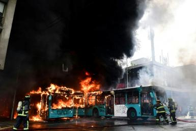 Chilean firefighters extinguish burning buses during clashes between protesters and the riot police in Santiago, on October 19, 2019.Chile's president declared a state of emergency in Santiago Friday night and gave the military responsibility for security