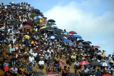 Rohingya refugees attend a ceremony marking the second anniversary of a military crackdown that prompted their exodus from Myanmar. Bangladesh authorities say thousands of refugees have agreed to be moved to an island in the Bay of Bengal