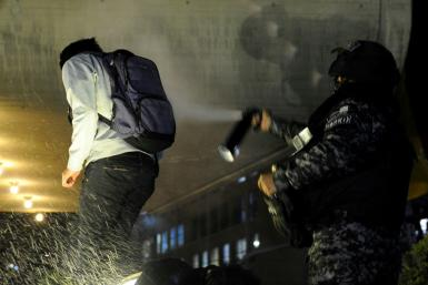 Riot police use pepper spray on a supporter of Bolivia's main opposition presidential candidate Carlos Mesa
