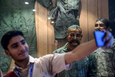 A Pakistan student in Karachi takes a selfie in front of the statue of Indian pilot Wing Commander Abhinandan Varthaman who was shot down over Kashmir earlier this year