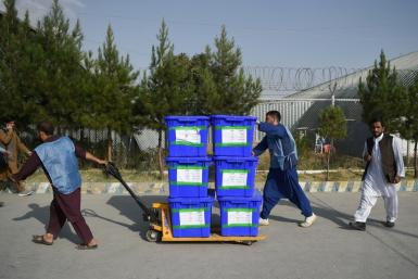 Independent Election Commission workers carry ballot boxes to a counting centre after the September poll