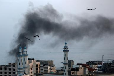 Smoke rises over Gaza City as Israel carries out a second day of air and missile strikes in response to barrages of rocket fire following its targeted killing of a top militant