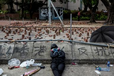 A Hong Kong pro-democracy protester sleeps on a barricaded street outside a university
