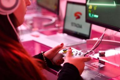 A visitor plays a game at the Google Stadia booth during the Gamescom trade fair in Cologne, Germany, on August 21