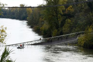 Rescuers search the Tarn river for survivors after a suspension bridge collapsed