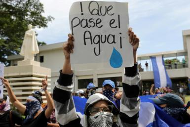 "A student carries a sign reading ""Let the water pass"" during a protest of students and relatives of political prisoners, in Managua on Tuesday"