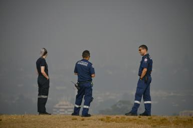 Paramedics take a break as they look out over a smokey haze which blankets Sydney.