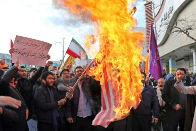 Iranian men burn a US flag during a protest in support of the Islamic republic's government and supreme leader Ayatollah Ali Khamenei