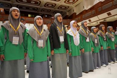 Students assembled in a university auditorium to practice ballads specially written for the pontiff