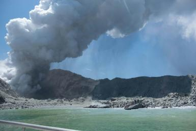 This handout photograph courtesy of Michael Schade shows the volcano on New Zealand's White Island spewing steam and ash minutes following a deadly eruption
