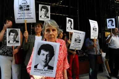 """Beatriz Cantarini de Abriata holds a portrait of her son Hernan, who is believed to have been the victim of the """"butcher"""" of Argentina's dictatorship Mario Sandoval, who has been arrested in France"""