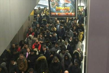 Commuters rush to board overcrowded trains to the Paris suburbs during rush hour
