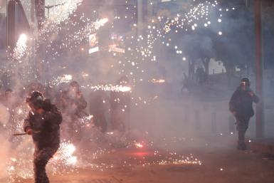 Lebanese counter-protesters threw firecrackers at riot police in central Beirut