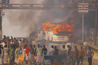 Protesters block a road after setting buses on fire during a demonstration against the Citizenship Amendment Bill in Howrah, on the outskirts of Kolkata
