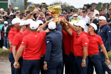 US team captain Tiger Woods (C, back to camera) and teammates celebrate with the trophy after winning the Presidents Cup golf tournament