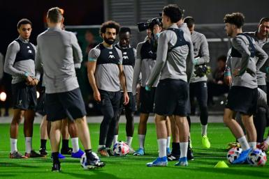Mohamed Salah (C) and his Liverpool teammates train in Doha on Monday as manager Jurgen Klopp watches on