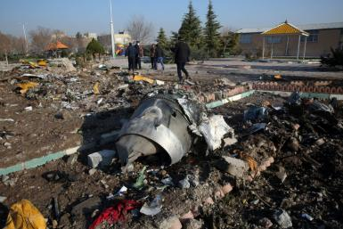 Rescue teams work among debris after a Ukrainian plane carrying 176 passengers crashed near Imam Khomeini airport in the Iranian capital Tehran