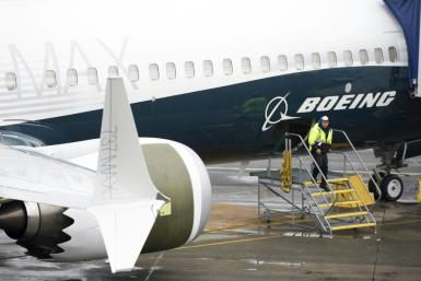 This file photo shows a Boeing worker next to a 737 MAX airplane on the tarmac at the Boeing factory in Renton, Washington