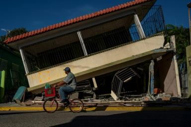 A man rides his bicycle past a collapsed house in Guanica, Puerto Rico on January 15, 2020, after a powerful earthquake hit the island