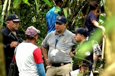Grab taken from Panamanian channel TVN Noticias showing Panamanian police and employees of the Public Ministry near the site where a mass grave was found with seven bodies at the indigenous region of Ngabe Bugle, in Bocas del Toro province, Panama, on Jan