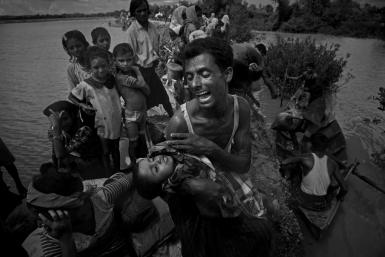 A Rohingya refugee reacts while holding his dead son after crossing the Naf river from Myanmar into Bangladesh on October 9, 2017, about two months after operations by the Myanmar military began