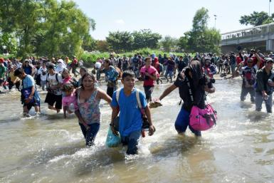 Central American migrants - mostly Hondurans, travelling on caravan to the US- cross the Suichate River, the natural border between Tecum Uman, Guatemala and Ciudad Hidalgo, Mexico, on January 20, 2020