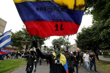 Protestors with their faces covered wave flags during a demonstration against the government of Colombia's President Ivan Duque in Bogota