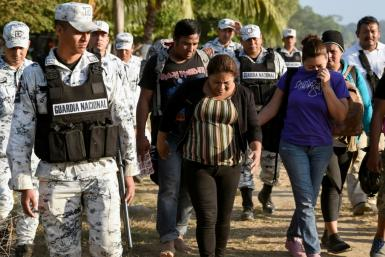 A Central American migrant family is escorted by members of the Mexican National Guard and officers of the Migration Institute after being detained crossing the Suchiate River, in Mexico