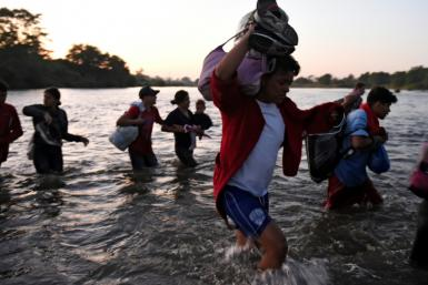 Central American migrants -- mostly Hondurans heading to the US in a caravan -- cross the Suchiate River from Tecun Uman, Guatemala, to Ciudad Hidalgo, Chiapas State, Mexico, on January 23, 2020
