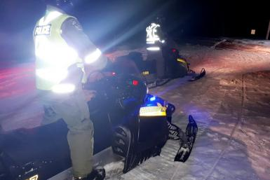 Police use snowmoblies during a search and rescue operations after a Canadian guide died and five French tourists went missing when their snowmobiles plunged through ice into the freezing water