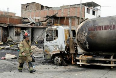 A fireman walks past the tanker truck that exploded in a Lima neighborhood on January 23, 2020, killing several people and igniting houses and cars