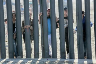Honduran caravan members look through through a fence at the US-Mexico border in San Ysidro, California in November 2018