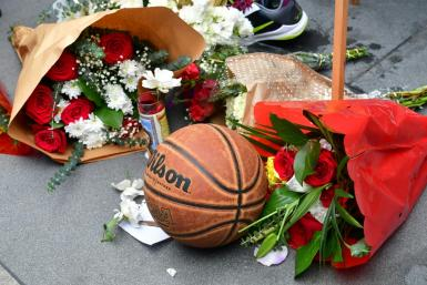 Fans gather around a makeshift memorial for former NBA and Los Angeles Lakers player Kobe Bryant after learning of his death at LA Live plaza near Staples Center in Los Angeles on January 26, 2020.
