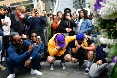 People gather around a makeshift memorial for former NBA and Los Angeles Lakers player Kobe Bryant after learning of his death at LA Live Plaza in front of the Staples Center in Los Angeles