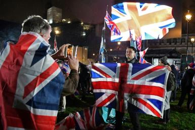 A Brexit supporter poses for a photograph with a Union flag as he waits for the festivities to begin in London on January 31, 2020, the day that the UK formally leaves the European Union