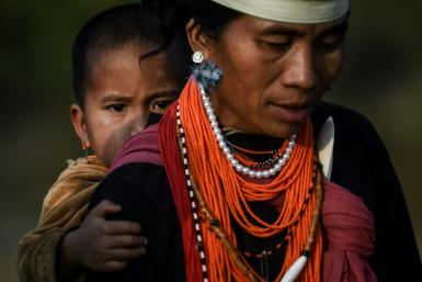 A Naga tribeswoman carrying a child at the end of an overnight ceremony to bless the harvest in Satpalaw Shaung village in Myanmar's Sagaing region