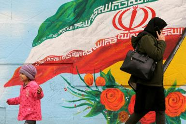 A woman and child walk past a mural with the Iranian national flag in Tehran