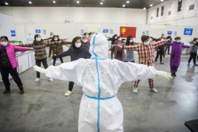 A medical staffer leads patients who have displayed mild symptoms of the COVID-19 illness in group exercises at a hospital in Wuhan, the epicenter of the global outbreak