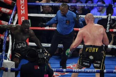 British boxer Tyson Fury, right, knocks American Deontay Wilder down before stopping him in the seventh round during their World Boxing Council heavyweight championship fight in front of a crowd of 15,800 at the MGM Grand Garden Arena in Las Vegas