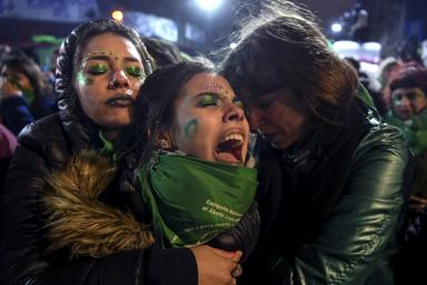 Activists in favor of abortion rights comfort each other outside the National Congress in Buenos Aires after senators rejected the bill to legalize the abortion in 2018
