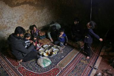 Darra lays down a large carpet for the family to share a frugal meal on the bare earth of the underground shelter